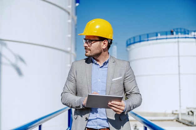 Dedicated caucasian unshaven supervisor in suit with helmet on head using tablet while standing on the bridge and looking away.