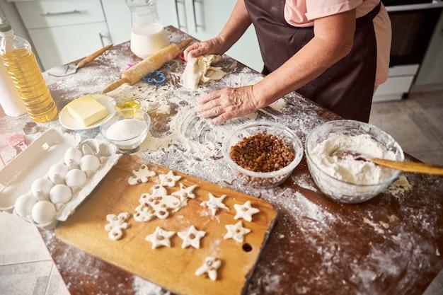 Преданная женщина-пекарь делает печенье на кухне