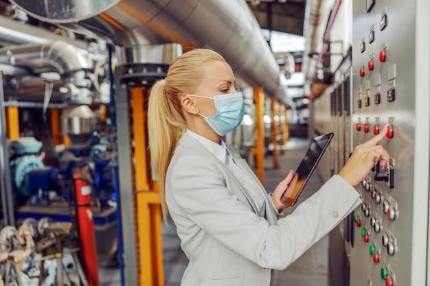 Выделенная женщина-блондинка-супервайзер с лицевой маской стоит на теплоцентрали рядом с приборной панелью, регулирует настройки и держит планшет во время пандемии коронавируса.