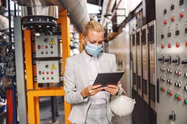 ダッシュボードの隣の暖房設備に立って、コロナパンデミック中に機械をチェックするためにタブレットを持っているフェイスマスクを持つ専用の女性の金髪の監督者。
