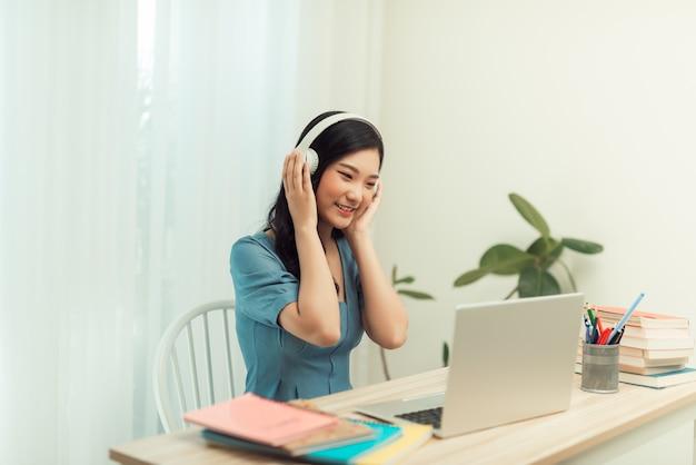 Выделенная женщина-фрилансер в очках и беспроводных наушниках улыбается в камеру, сидя за ноутбуком с кружкой