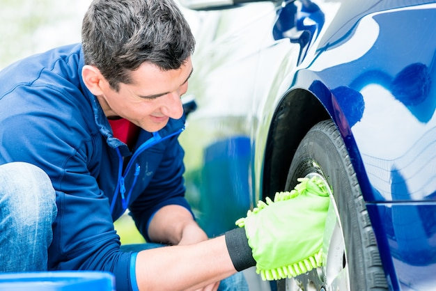 屋外でリムを掃除するためにマイクロファイバー洗車ミットを使用する熱心な男性労働者