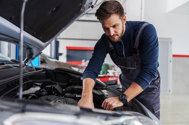 Dedicated mechanic fixing car motor while standing in garage of car salon.