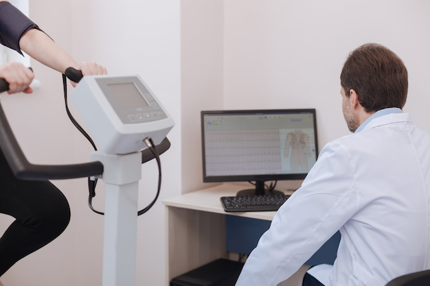 Dedicated professional young cardiologist using his computer observing numbers of patients physical performance and making conclusions