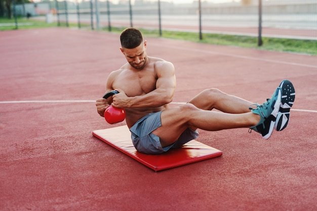 Dedicated shirtless muscular caucasian man with short haircut sitting on the mat and doing exercises with kettlebell. outdoor fitness concept.