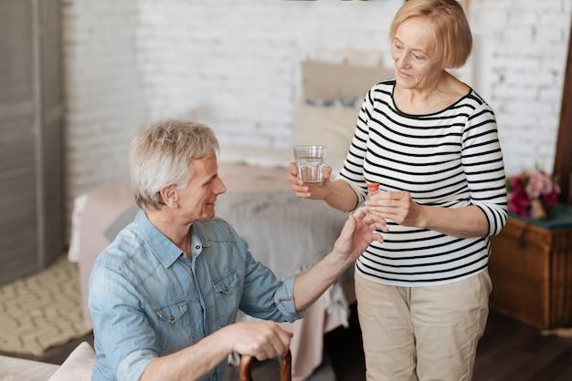 Посвященный супругу. посвященная милая зрелая женщина дает своему мужчине упаковку таблеток и стакан воды для приема, помогая ему во время выздоровления
