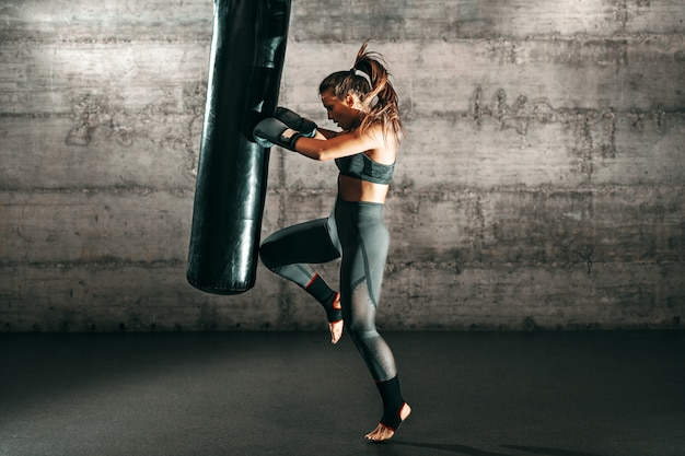 Dedicated strong brunette with ponytail, in sportswear, bare foot and with boxing gloves kicking sack in gym.