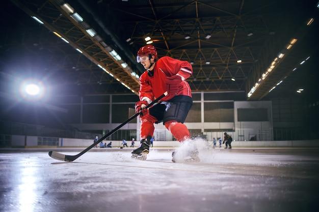 ホールの氷の上でホッケーをする熱心な白人のハンサムなホッケー選手。