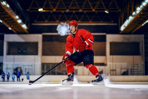 Dedicated strong hockey player in red uniform with protective helmet on head skating and going to goal with stick and puck.