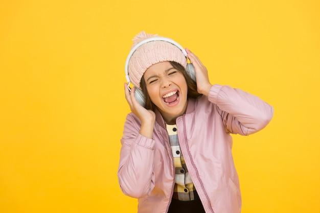 Посвящается пению. маленькая певица на желтом фоне. счастливая девушка любит петь под музыку. урок пения. вокальные упражнения. научитесь петь. музыкальная школа. ее певческий голос действительно прекрасен.