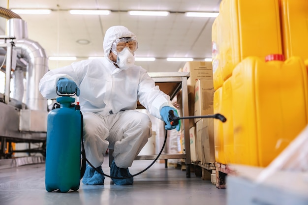 Dedicated worker in protective white uniform with rubber gloves holding sprayer with disinfectant and spraying while crouching in warehouse.