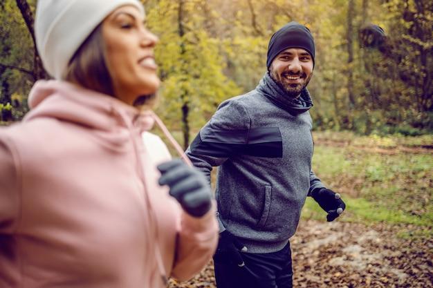 寒い天候で自然に並んで実行されているスポーツウェアの専用のスポーティなカップル。