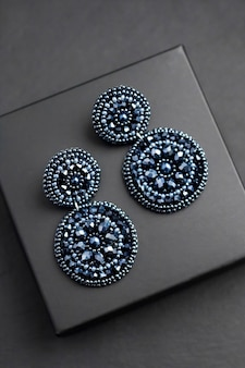 Deep blue beads embroidered earrings on black surface