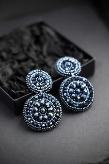 黒い表面に深い青色のビーズが刺繍されたイヤリング