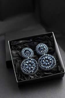 Серьги, вышитые темно-синим бисером на черной поверхности Premium Фотографии