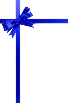 Deep blue gift ribbon bow vertical top corner border frame isolated on white.