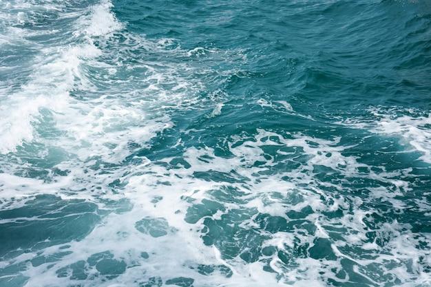 Глубокая синяя поверхность морской воды с белым рисунком пены и волн