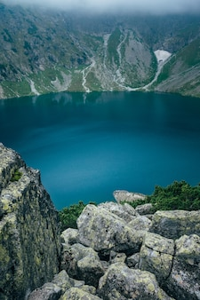 Deep blue surface lake in mountain mist landscape. tatra mountains, czarny staw, poland