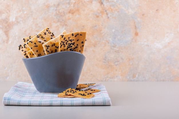 Deep bowl of crackers with black seeds on white background. high quality photo