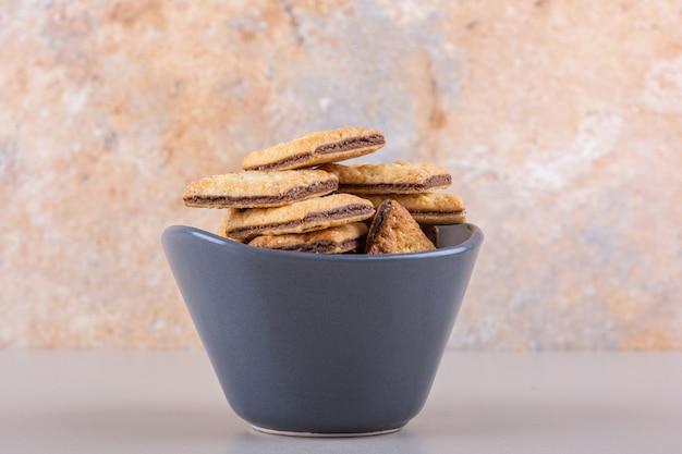 Ciotola profonda con biscotti ripieni di cioccolato su sfondo bianco. foto di alta qualità