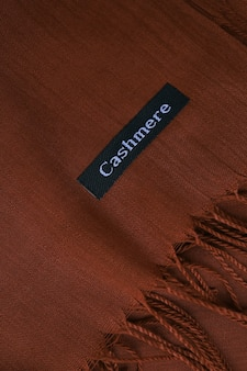 Deep brown cashmere texture chocolate textile background fabric label on coffee cashmere scarf mater...