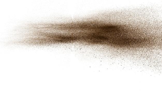 Частицы глубокого коричневого цвета забрызгали на белом фоне. коричневая пыль.