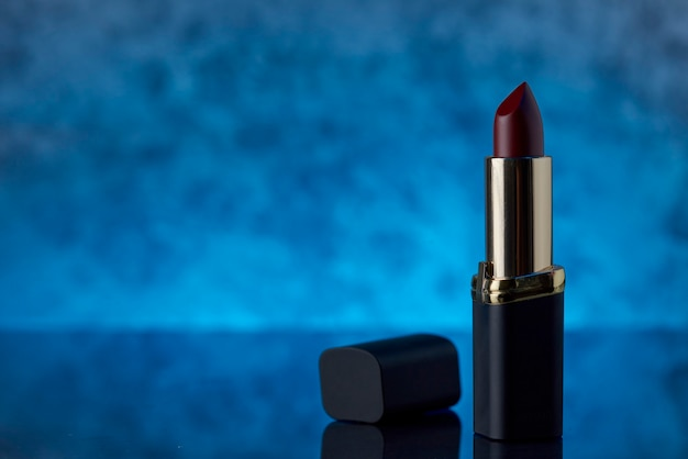 Deep burgundy lipstick on a marble surface with a blue background