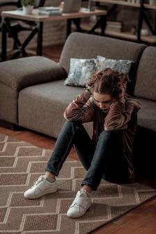 深い憂鬱。深いうつ病を抱えながら床に座っている白いスニーカーを履いた 10 代の少女