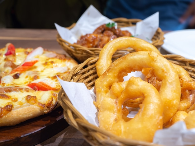 Deep fried chicken in a basket with parsley and seafood pizza topping with crab