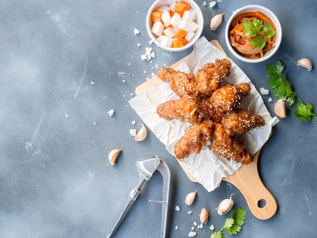 韓国風のガーリックソースを添えた手羽先の揚げ物は、アジア料理のコンセプトのコピースペースを備えた上面図の灰色の背景にキムチと大根のピクルスを添えて提供しています。