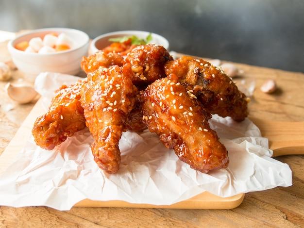 韓国風のガーリックソースで揚げた鶏の羽は、アジア料理のコンセプトのために木製のテーブルにキムチと大根のピクルスを添えて提供しています。