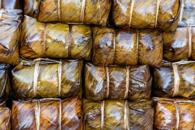 タイの屋台の食べ物市場で緑のパンダンの葉に包まれたフライドチキン