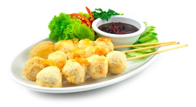 串焼きのクリスピーポークボールの炒め物フライチリスパイシーソースディッピングタイの屋台の食べ物人気のある装飾野菜と刻まれた唐辛子の側面図