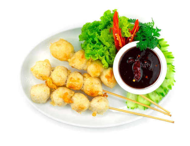 串焼きのクリスピーポークボールの炒め物フライチリスパイシーソースディッピングタイの屋台の食べ物人気のある装飾野菜と刻まれた唐辛子のトップビュー
