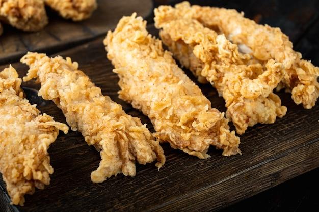 Deep fried crunchy spicy chicken meat on dark wooden table.