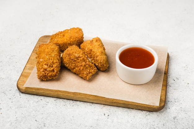 Обжаренные во фритюре куски мяса и соус