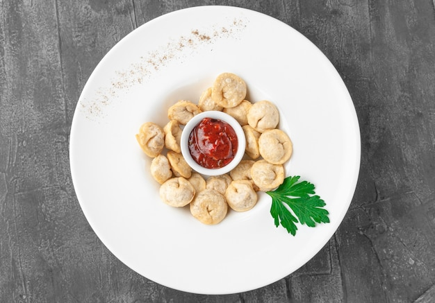 Deep-fried dumplings with tomato sauce. in a large white plate. decorated with parsley. view from above. gray concrete background.