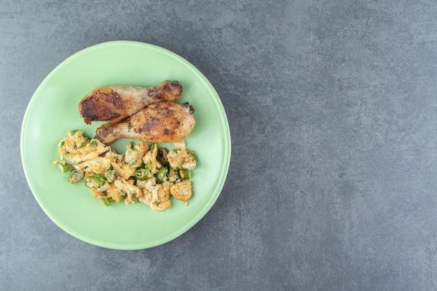 Uova fritte e cosce di pollo sul piatto verde.
