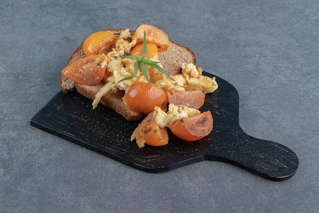 Яичница во фритюре с помидорами и хлебом на черной доске.