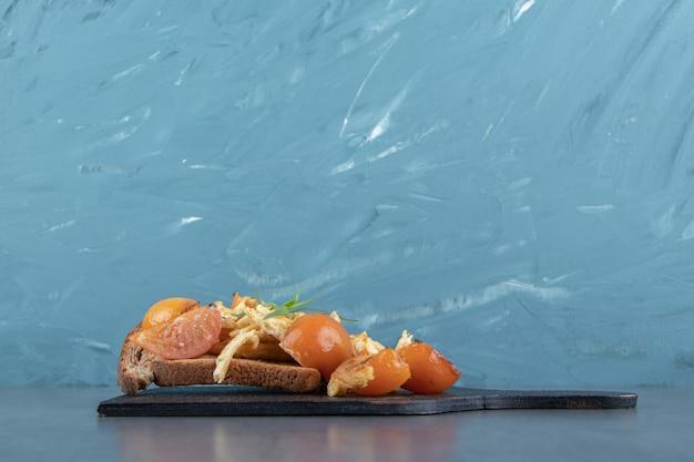 Uova fritte con pomodoro e pane su tavola nera