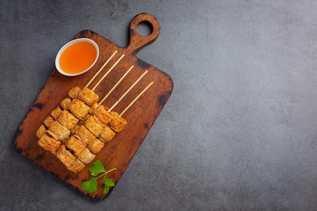 Rotolo di pollo fritto sulla superficie scura.