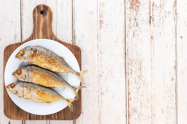 오래된 흰색 나무 질감 배경의 나무 커팅 보드에 있는 흰색 세라믹 접시에 튀긴 고등어 생선, 텍스트 복사 공간, 위쪽 전망, 유명한 태국 음식 pla too tod