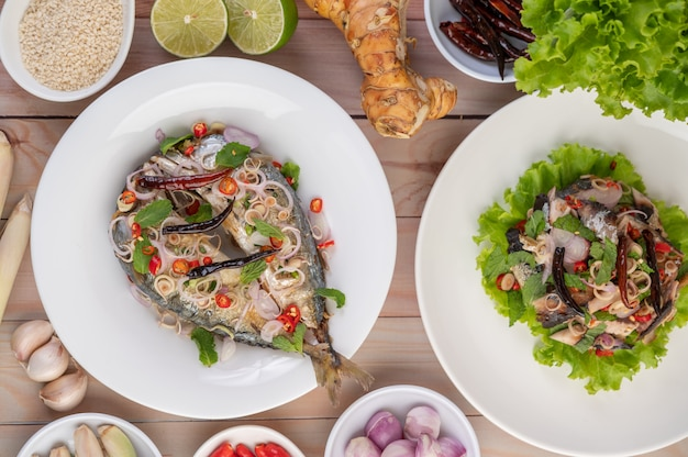 Deep-fried mackerel topped with galangal, pepper, mint, red onion in a white dish.
