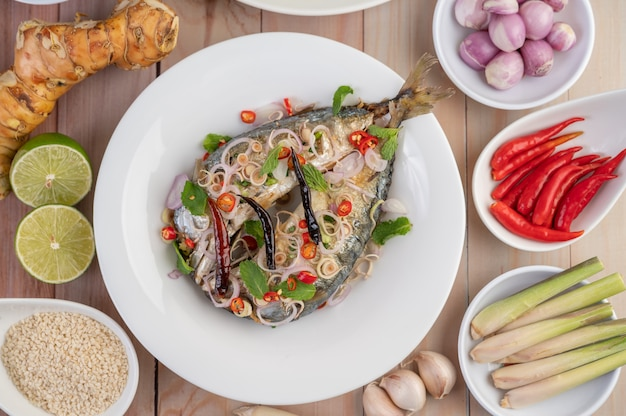 Deep-fried mackerel topped with galangal, pepper, mint, red onion in a white dish. Free Photo