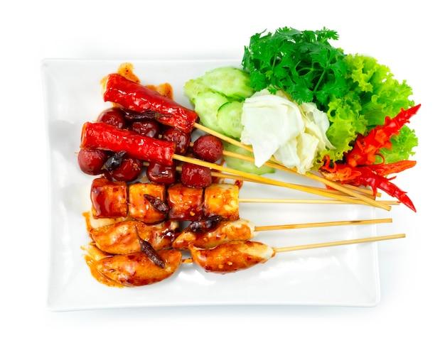 Жареные во фритюре фрикадельки на шпажках с острым соусом из жареного чили тайская уличная еда популярное украшение овощи и резной перец чили topview