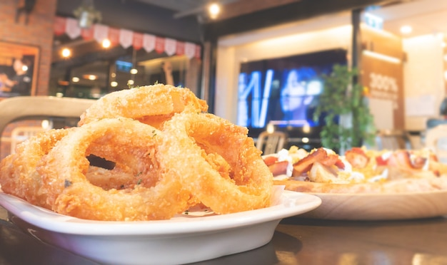 Deep fried onion ring serve along side with pizza