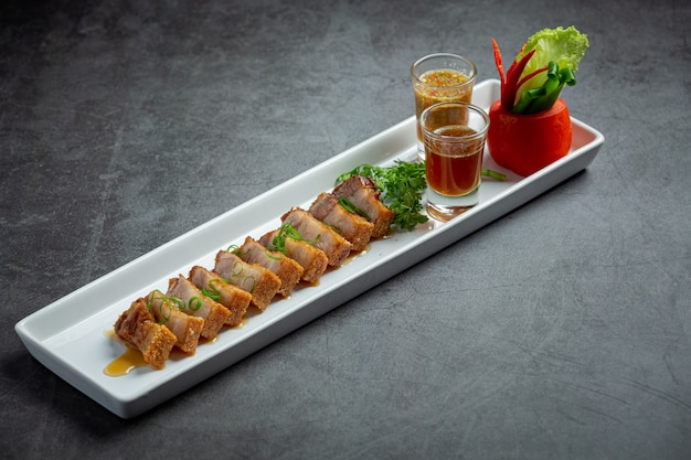 Deep fried pork belly with fish sauce on dark background
