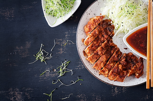 Deep-fried pork chop with cabbage and tonkatsu sauce.