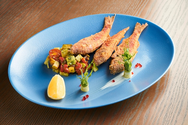 Deep-fried red mullet fish on a blue ceramic plate on a wooden surface. restaurant serving fish with salad. close up view on tasty seafood. film effect during post. soft focus