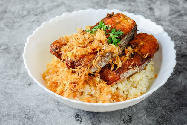 Deep fried sliced pangasius fish with garlic, served with brown rice.